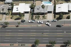 Dave Uribe's patrol car is in the center of the photo; his vest and gun belt are on the pavement 15 feet ahead.