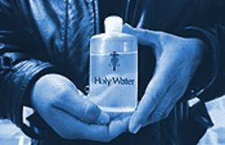 Hernandez holds his most prized spiritual weapon, a bottle of holy water, consecrated by Roman Catholic priests.