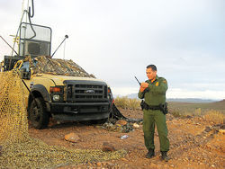 A Border Patrol surveillance truck sits camouflaged atop a hill in southeastern Arizona. The truck employs a camera that senses body heat to help agents spot immigrants from as far away as seven miles.