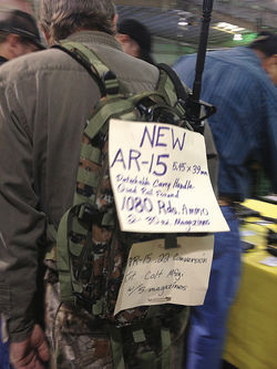 One of several people selling assault rifles off their backs at the Crossroads of the West gun show at the Arizona State Fairgrounds on January 20.