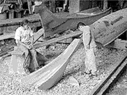Carl Martin, left, and a friend look over the traditional canoes Carl and his brother, Joe, make for use by other tribes.