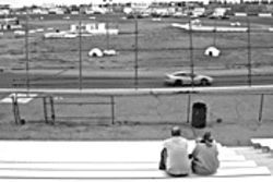 Spectators watch cars emulate the Japanese motor sport of drifting.