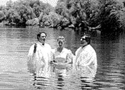 Elim church pastors Dorel Michula, left, and Dorin Druhora baptized Eva Farkas during a 1997 ceremony at Estrella Lake.