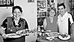 Global gourmets: Mercedes Rodas (far left) of Hugo's Salvadorean with platters of pupusas; and Cafe Sarajevo's Seida and Dean Turulja with a Bosnian feast.