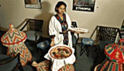 Keepin' it real: Owner/chef Tina Tamrat Hildebrand, in a traditional Ethiopian dress, before a messob full of Ethiopian eats.