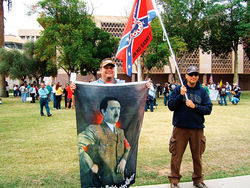 Ready with a portrait of Adolf Hitler outside a nativist rally at the state Capitol