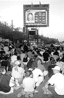 Enthusiastic Diamondbacks fans sit in the street to watch the game outside of the sold-out Bank One Ballpark.